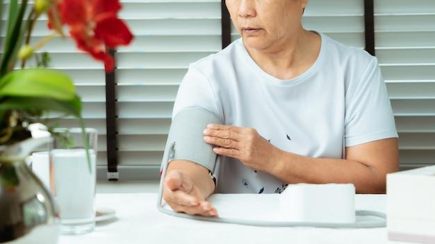 Старшая женщина обнаруживает давление крови дома Premium Фотографии