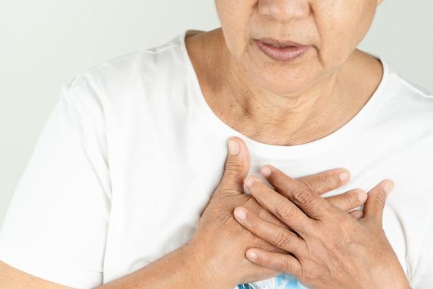 Сердечный приступ старухи держа грудь Premium Фотографии