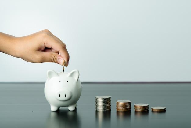 お金の節約と寄付のコンセプト、子供はかわいい白い貯金箱にお金を置く Premium写真