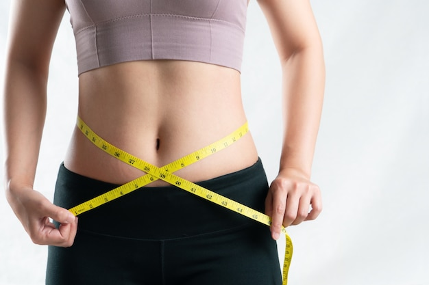 若い女性がメジャーテープ、女性の食事療法のライフスタイルのコンセプトで彼女の腹の腰を測定 Premium写真