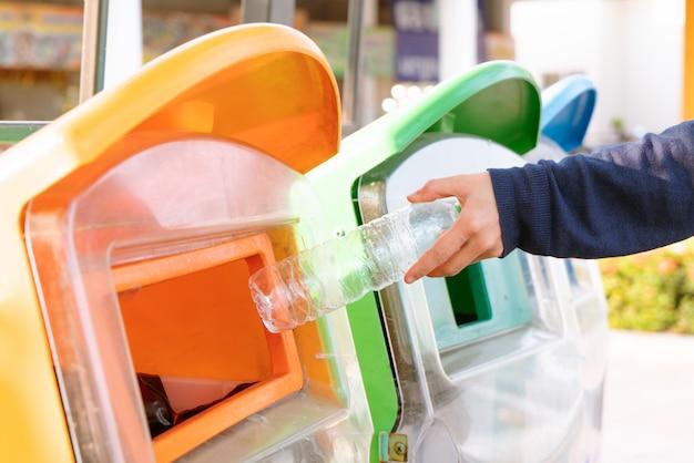 ゴミ箱に捨てる前にゴミ/ゴミを分別し、ゴミ/ゴミを分別する女性の手 Premium写真