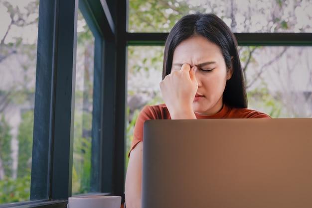 Усиленная головная боль коммерсантки работая на портативном компьютере. негативные эмоции человека выражение лица чувства Premium Фотографии