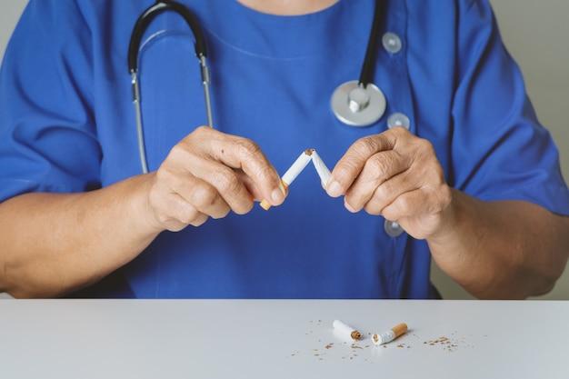 Бросай курить, дня без табака, доктор ломает сигарету Premium Фотографии