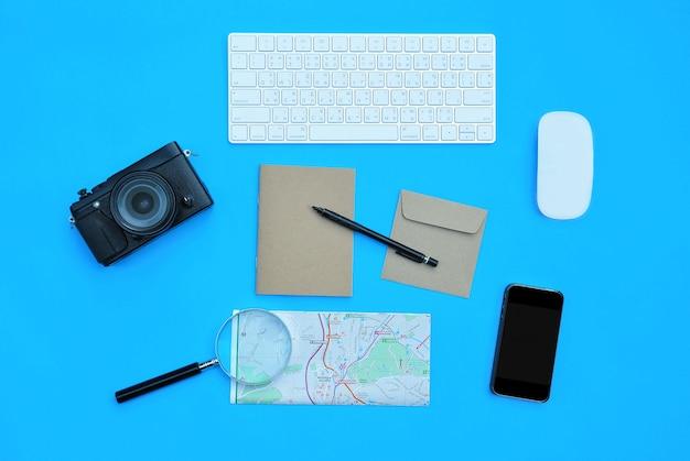 青い机の背景にアクセサリーのフラットレイアウト Premium写真