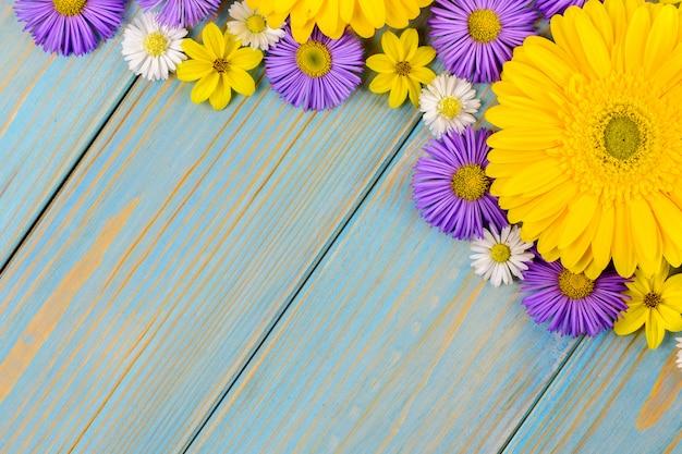 Желтые цветы герберы, ромашки и фиолетовый сад на синий деревянный стол. Premium Фотографии