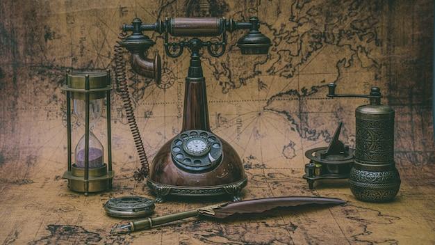 レトロなブロンズ電話と古い世界地図上の古いコレクション Premium写真