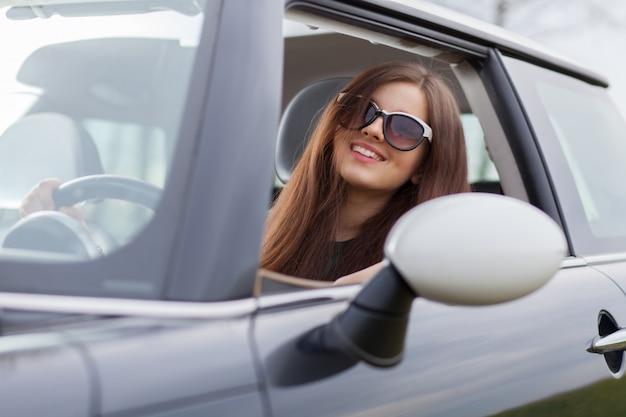 車を運転する若い美しい女性 Premium写真