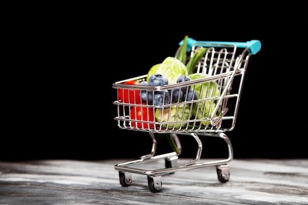 黒の背景に野菜と一緒に買い物カゴ Premium写真