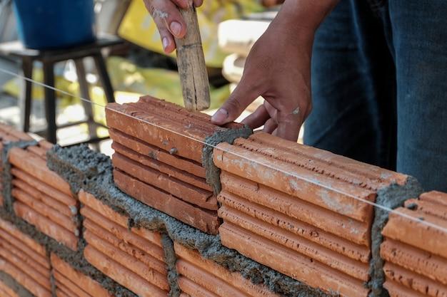 Работник каменщика устанавливая кирпичную кладку на внешнюю стену. Premium Фотографии
