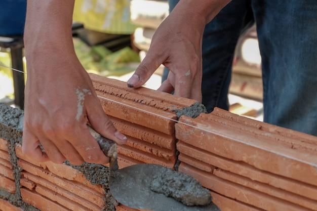 れんが造りの労働者が外壁にれんが造りの石積みをインストールします。 Premium写真
