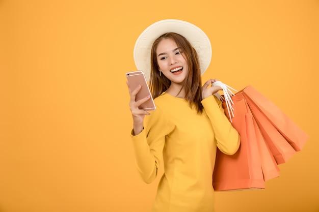 美しい女性は青い紙袋で夏に買い物をしています Premium写真