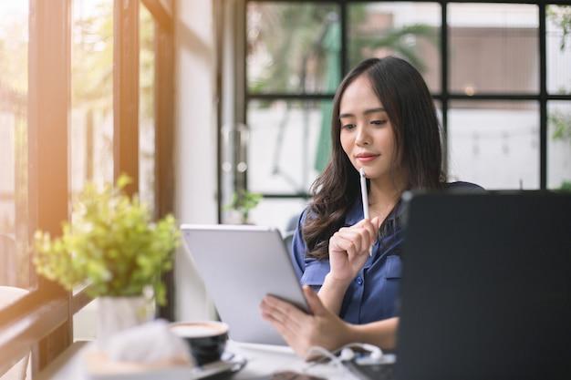アジアの女性はタブレットを運ぶノートを持っていて、喫茶店で笑顔で考えています。 Premium写真