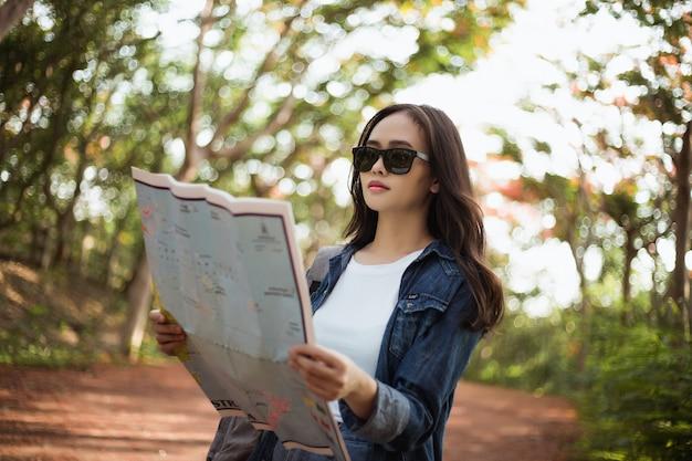 バックパックと流行に敏感な女性はタイのジャングルの中で夏に旅行しています。 Premium写真