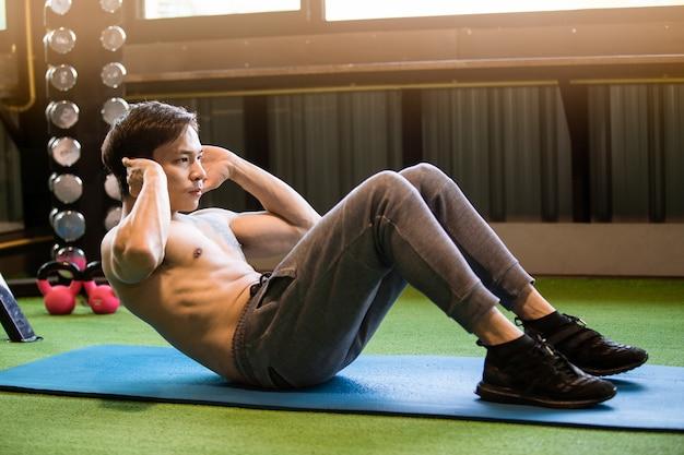筋肉のアジア人が運動をして運動します。 Premium写真
