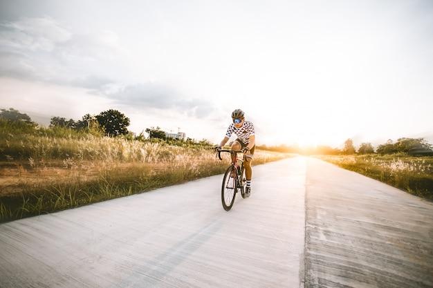 アジア人男性のサイクリストが夕日に開いた道で自転車に乗って。 Premium写真