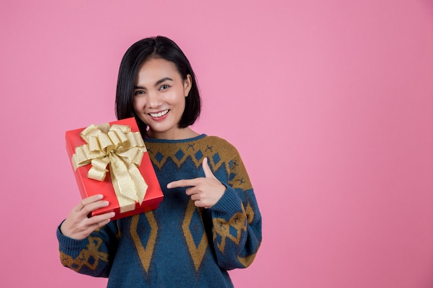 ピンクの背景にギフトを持つアジアの女性。 Premium写真
