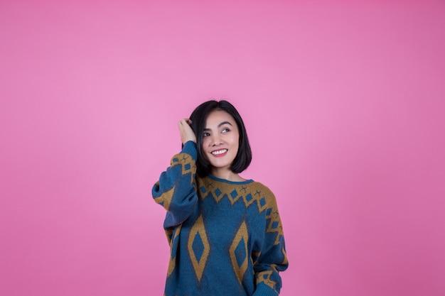 ピンクの背景でとても美しいアジアの女性。 Premium写真