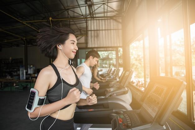 アジアの若い筋肉、トレッドミルで実行されています。 Premium写真