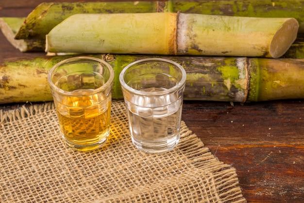 カシャーサは、ブラジルで生産されたサトウキビで作られた典型的なアルコール飲料の名前です。木製のテーブルにブラジルの伝統的な飲み物 Premium写真