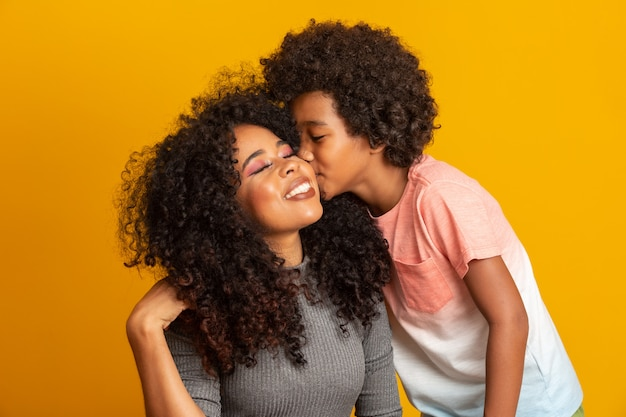 Портрет молодой афро-американской матери с сыном малыш. сын целует маму. желтая стена. бразильская семья. Premium Фотографии