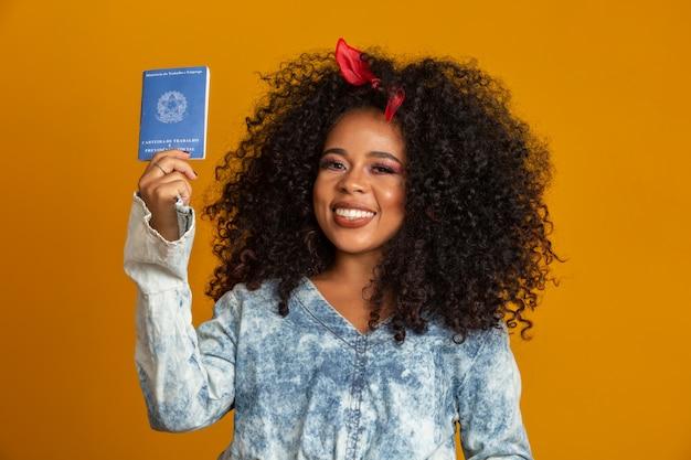 作業カードを保持している美しい縮れ毛の少女。黄色の壁に。 Premium写真