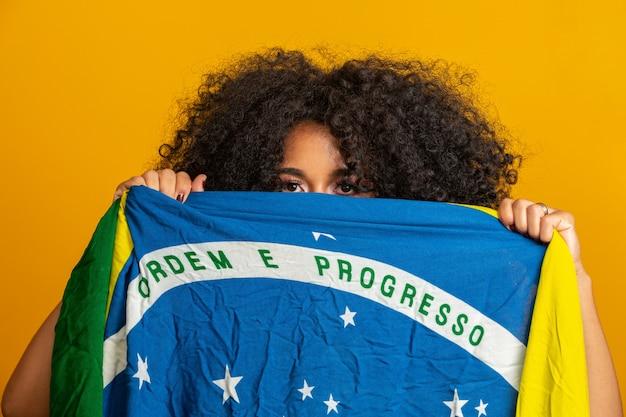 Таинственный черный фанат женщина держит бразильский флаг в вашем лице. бразилия цвета в стене, зеленый, синий и желтый. выборы, футбол или политика. Premium Фотографии