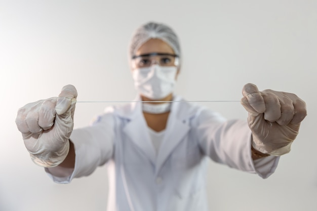 フロスの切れ端を提示する歯科医、歯をきれいにするための新しい技術の開発 Premium写真