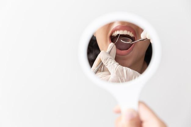 歯科医の鏡による口腔診査中の患者の開口部。閉じる。 Premium写真