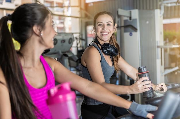 美しい女性がジムでトレーニングします。明るくモダンなジムでトレッドミルで運動する若い女性の友人の美しいグループ。 Premium写真