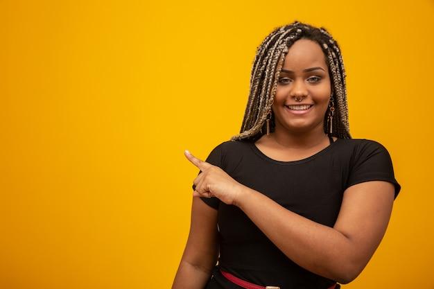 黄色の指を指している怖い髪の美しい若いアフリカ系アメリカ人女性 Premium写真