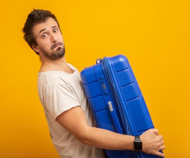 Забавный мужчина держит тяжелую сумку на желтом Premium Фотографии