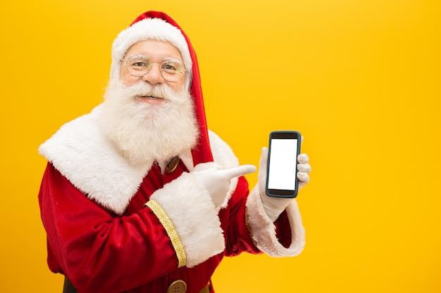 黄色の背景に携帯電話でサンタクロース Premium写真