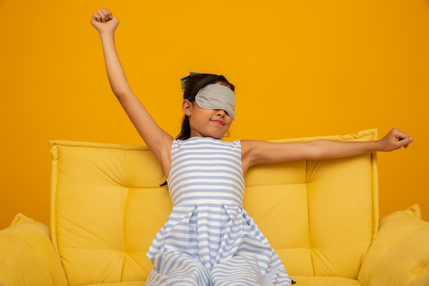 Азиатский ребенок спит на диване с маской для сна Premium Фотографии