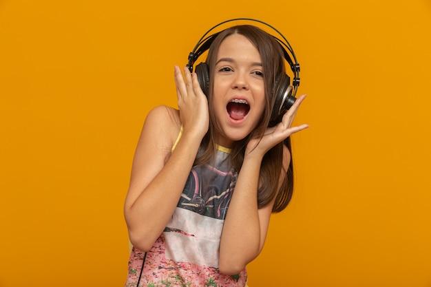 ヘッドフォンを持つ若い女 Premium写真