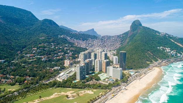 Вид с воздуха на фавела да росинья, самая большая трущоба в бразилии на горе в рио-де-жанейро, и горизонт города позади Premium Фотографии