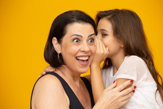 Мама и дочь делятся секретом Premium Фотографии