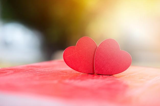 Два деревянных сердца на красном деревянном столе размытые, выражение любви, праздник валентина, концепция любви Premium Фотографии