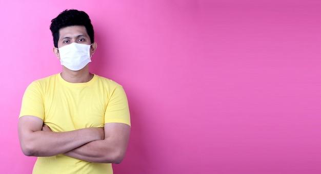 Азия мужчины в маске, изолированные на розовом фоне в студии Premium Фотографии