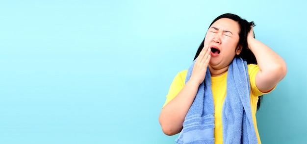 スタジオで青い背景にシャワーを浴びて歩いている間、アジアの女性の肖像画は眠い感じ Premium写真