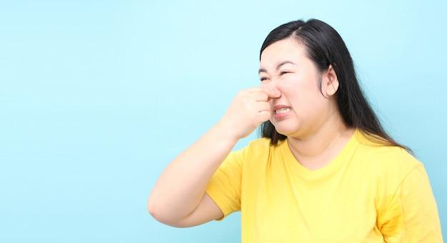 アジアの女性の肖像画は、スタジオで青色の背景に、ファウルを感じています Premium写真