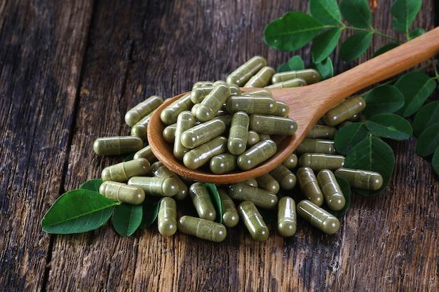 Травяные капсулы из листьев моринга на деревянной ложке Premium Фотографии