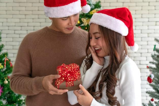 女の子のクリスマスプレゼントを与える男 Premium写真