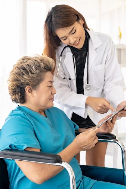 Доктор используя таблетку с старым пациентом Premium Фотографии