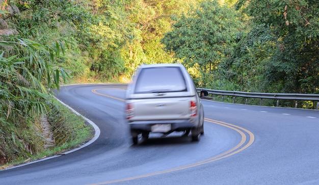 曲線道路でぼやけた車の運転 Premium写真