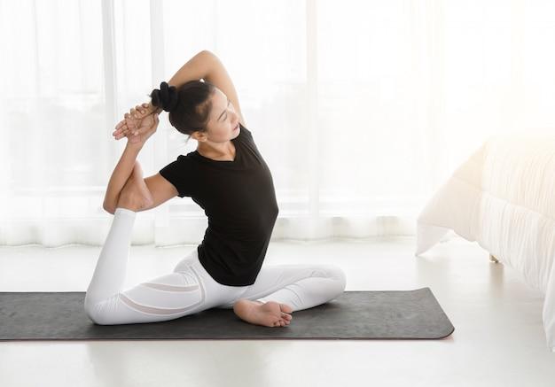 アジアの女性は、ヨガを練習して、寝室で人魚の運動やエカパダラジャカポタサナポーズを行う Premium写真