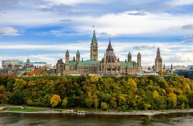 議会の丘とオタワ、カナダのオタワ川の秋景色 Premium写真