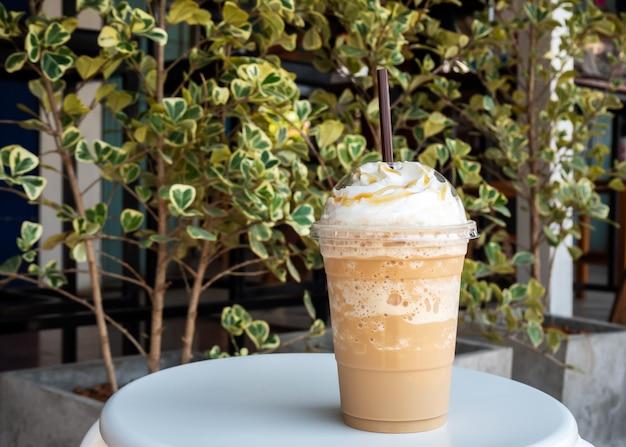 カプチーノをプラスチック製のコップにブレンド。ホイップクリームを添えて。飲み物を飲みます。好きなカフェイン飲料。 Premium写真
