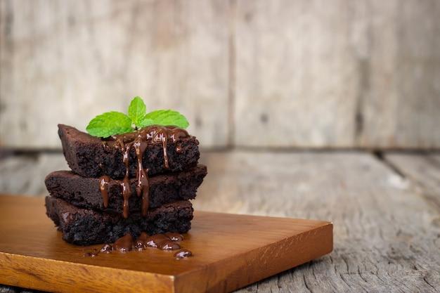 自家製ブラウニーにチョコレートファッジを添えています。木製の背景に甘いデザート。 Premium写真
