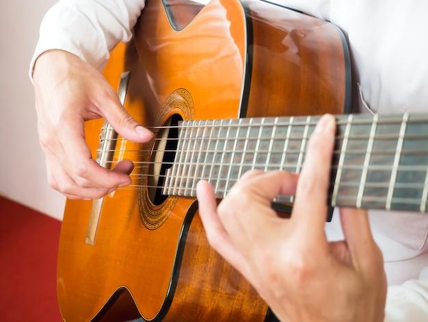 男はギターを弾く。クラシック音楽楽器。弦楽器。 Premium写真