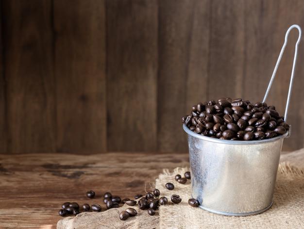 亜鉛メッキのローストコーヒー豆缶グランジの木製の背景の上 Premium写真